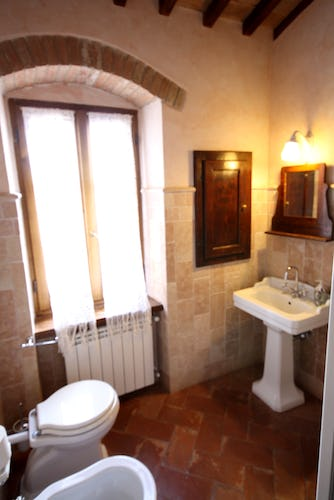 Bathroom with terracotta floors & wooden beamed ceilings