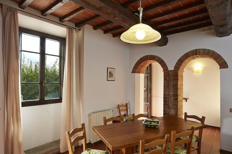 The furnishings are in Tuscan rural style, with exposed wooden beamed ceilings, a classic in Tuscan country homes