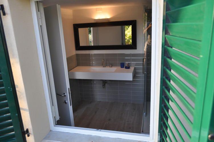 Il bagno, anch'esso arredato in stile moderno con una grande finestra