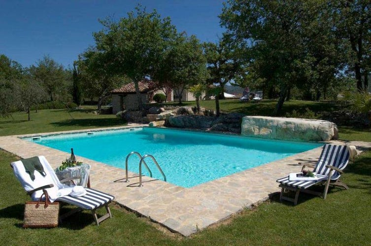 Private holiday swimming pool with lounge chairs and tables