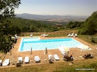 Large family friendly pool with umbrellas and chaise lounges