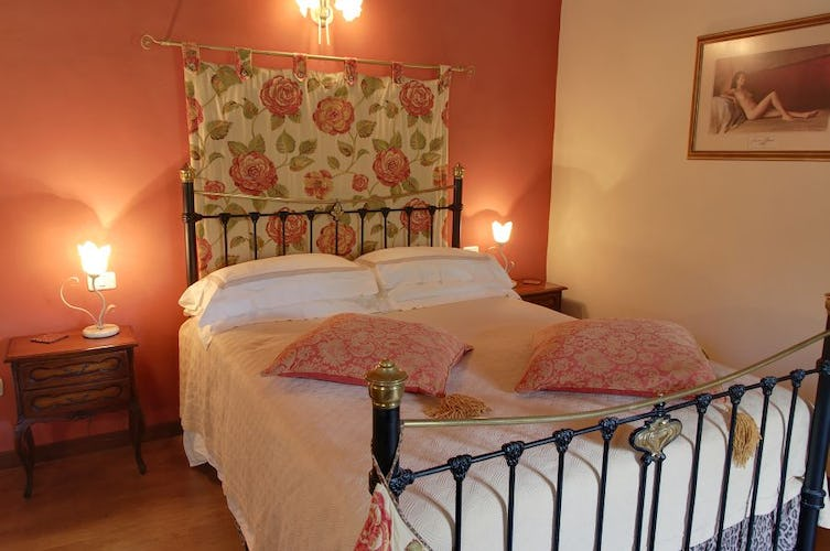 Warm wood floors, and wrought iron bedstands decorate the bedrooms