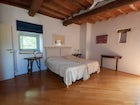 Comfortable wooden floors accent the luminous bedrooms at Montrogoli