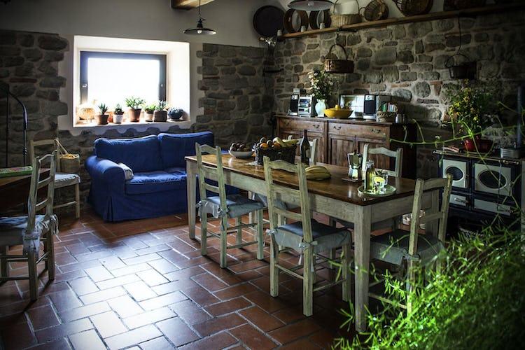 Il salotto con il camino in stile rustico e la scala a chiocciola